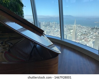 San Francisco, CA/USA - July 31 2019: Baby grand piano and the aerial view of the city skyline from the observation deck. Golden Gate Bridge and the Transamerica pyramid in the background.