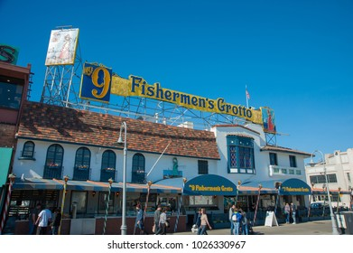 SAN FRANCISCO, CA/USA - FEBRUARY 03, 2018: Tourists visit San Francisco's Fisherman's Wharf District with Fisherman's Grotto restaurant in the background