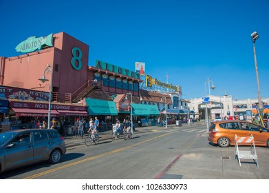 SAN FRANCISCO, CA/USA - FEBRUARY 03, 2018: Tourists visit San Francisco's Fisherman's Wharf District with Fisherman's Grotto and Alioto's restaurants in the background
