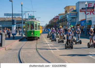 SAN FRANCISCO, CA/USA - FEBRUARY 03, 2018: Tourists tour San Francisco's Fisherman's Wharf area on Segways as others walk, or use the trolley