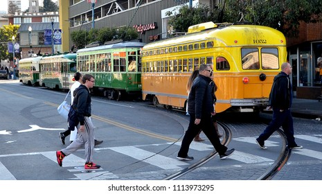 San Francisco, CA/USA-November 26, 2015: Pedestrians walking in a crosswalk with several colorful vintage streetcars in the background on Jones Street near Fisherman's Wharf in San Francisco.