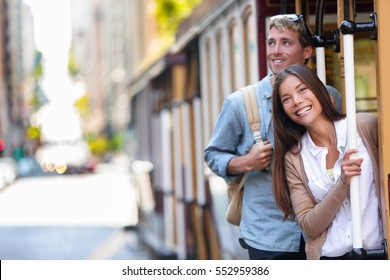 San Francisco city tourists riding cable car tramway tourism people lifestyle. Young interracial couple enjoying ride of cable car railway system, popular travel attraction.