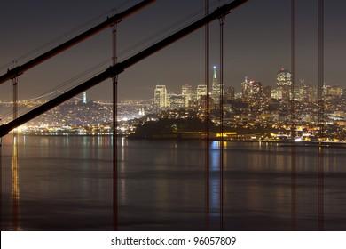 San Francisco downtown seen through Golden Gate Bridge's cables.