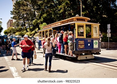 SAN FRANCISCO - JULY 22: Passengers enjoy a ride in a cable car on July 22, 2011 in San Francisco. It is the oldest mechanical public transport in San Francisco which is in service since 1873.