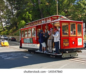 SAN FRANCISCO - JUN 20: Tourists ride a cable care in San Francisco followed by a small touring car. Taken June 20, 2012 in San Francisco, CA.