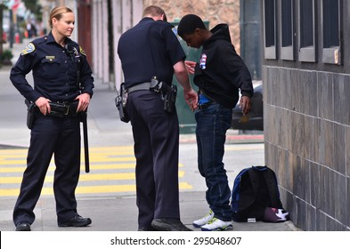 SAN FRANCISCO - MAY 15 2015:SFPD officers patdown black american man in San Francisco.Overall, Black Americans are arrested at 2.6 times the per-capita rate of all other Americans.