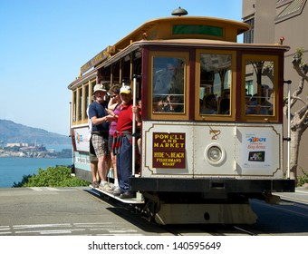 SAN FRANCISCO, MAY 2 - Unidentified people traveling in a cable car with Alcatraz visible in background, May 2, 2013, San Francisco, United States.