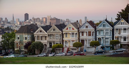 """San Francisco - May 20 2012: The famous """"painted ladies"""" townhouse with the backdrop of San Francisco downtown at dusk."""