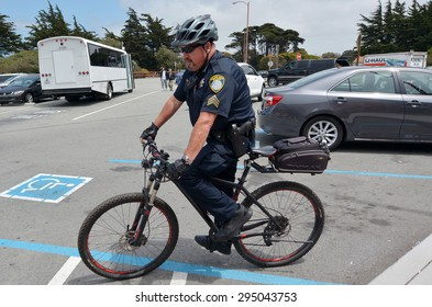 SAN FRANCISCO - MAY 20 2015:SFPD officer patrol on a bike in San Francisco.During police operations many criminals do not realize that an approaching person on a bike is actually a police officer.