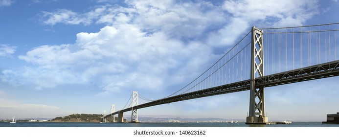 San Francisco Oakland Bay Bridge with White Puffy Clouds on Blue Sky Panorama