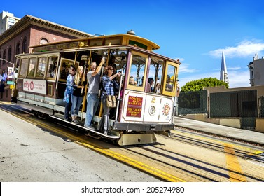 SAN FRANCISCO - OCT 06: Passengers enjoy a ride in a cable car on Oct 06, 2012 in front of famous Transamerica building in San Francisco. Oldest mechanical public transport. In service since 1873.