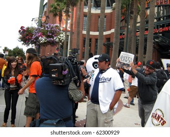 SAN FRANCISCO - OCTOBER 2: Padres Fan interviewed by News-reporter with Giants Fans celebrating winning division behind him. On October 3 2010 at Att Park in San Francisco California.