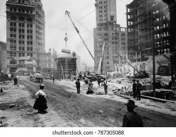 San Francisco rebuilding after the April 18, 1906 earthquake and fire. A crane is moving rubble, as several men and a woman walk by in 1906