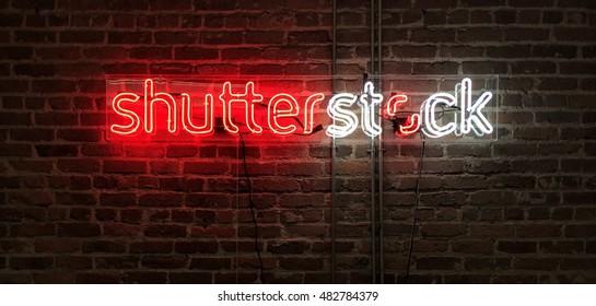 SAN FRANCISCO, 13 de setiembre de 2016 — Signo neón del logo de Shutterstock brillando contra una pared de ladrillo expuesto en la oficina de Shutterstock, Inc. en San Francisco (NYSE): SSTK).