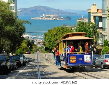 SAN FRANCISCO - SEPT. 17, 2012:  A San Francisco trolley descends Hyde Street to Fisherman`s Wharf and the ferry to Alcatraz island.