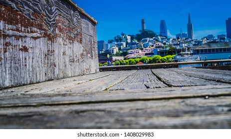 San Francisco skyline from fisherman's wharf. Weathered wood blue skies cityscape coit tower, Transamerica pyramid and sales force tower. May 2019