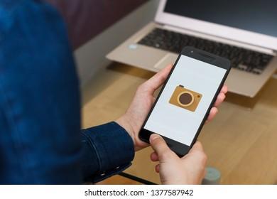 SAN FRANCISCO, US - 22 April 2019: Close up to female hands holding smartphone using Google Cardboard Camera application, San Francisco, California, USA. An illustrative editorial image