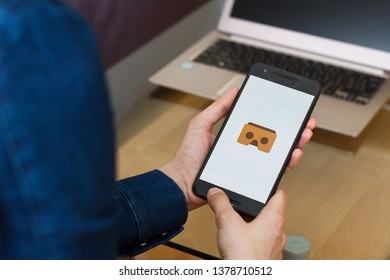 SAN FRANCISCO, US - 22 April 2019: Close up to female hands holding smartphone using Cardboard application, San Francisco, California, USA. An illustrative editorial image