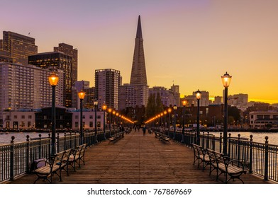 San Francisco, USA - February 22, 2014: Scenic view onto Embarcadero Buildings, decorated for Christmas, downtown San Francisco and Transamerica Pyramid from famous romantic wooden Pier 7 at sunset