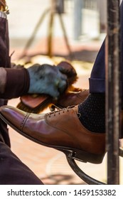 San Francisco, USA - July 10, 2019, Shoeshiner polishes a client's shoes with a shoe brush, close-up view, with a blurred depth of field. Concept, street artisans, masters.