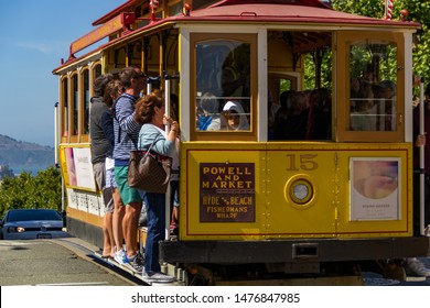 San Francisco, USA - July 18, 2019, people hang in the old tram on the cable car in the city of San Francisco, close up view, in clear sunny weather, concept, tourism, travel, vintage, retro transport