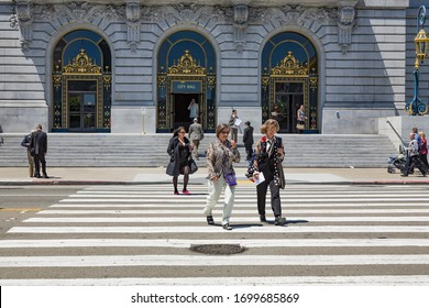 San Francisco, USA - July 23, 2008: people crossing the street at the pedestrian crossing in front of the City Hall in San Francisco, USA. City Hall is the seat of government for the City.