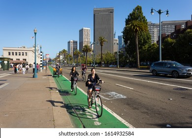 San Francisco - USA - July 5 2017: Young people ride bicyles front of the Embarcadero waterfront in San Francisco in California.