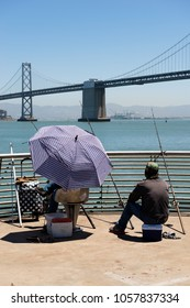 San Francisco, USA - June 23, 2015: People fishing near Bay Bridge
