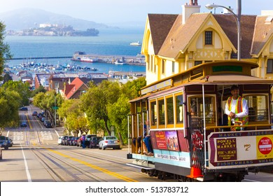 San Francisco, USA - May 10, 2016: Brakeman appying cable car brakes going downhill on steep Hyde Street hill with sweeping view of Alcatraz Prison, bay water and Victorian house on sunny summer day