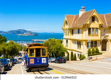 San Francisco, USA - May 15, 2016: Blue cable car with hanging tourists going uphill on steep Hyde St with sweeping view of Alcatraz Prison, bay water and yellow Victorian house on sunny blue sky day