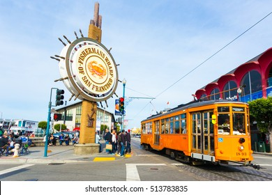 San Francisco, USA - May 5, 2016: Orange vintage Swiss F Market streetcar rolls by large sign at entrance to tourist attraction of Fisherman's Wharf on the corner of Beach and Jones Street. Horizontal