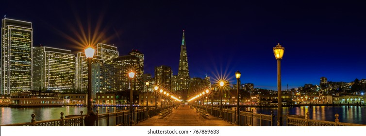 San Francisco, USA - November 27, 2017: Panoramic view of Embarcadero Buildings, decorated for Christmas, downtown San Francisco and Transamerica Pyramid from famous romantic wooden Pier 7 at sunset