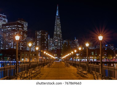 San Francisco, USA - November 27, 2017: Scenic view of Embarcadero Buildings, decorated for Christmas, downtown San Francisco and Transamerica Pyramid from famous romantic wooden Pier 7 at sunset