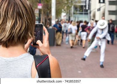 San Francisco, USA -  September 13th, 2017: A woman is recording a video with her mobile phone of a street performer costumed like Michael Jackson, San Francisco.