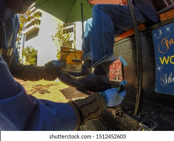 San Francisco, USA - September 18, 2019, a shoe-polisher rubbing and polishing a client s shoes with a brush and special shoe care products, close-up view with a fisheye effect. Concept, street