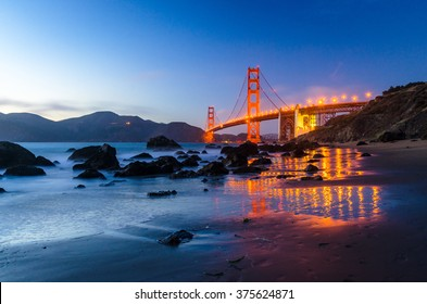 SAN FRANCISCO, USA - SEPTEMBER 2, 2015: Golden Gate Bridge during the sunset, view from the beach, water reflects the lights