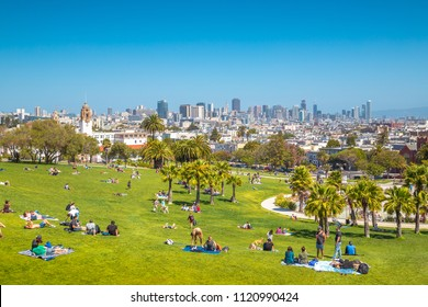 SAN FRANCISCO, USA - SEPTEMBER 4, 2016: People enjoying the sunny weather in Mission Dolores park on a beautiful day with clear blue skies with the skyline of San Francisco in the background