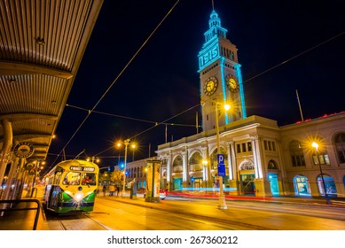 San Francisco vintage f- streetcar, tram or muni cable trolley car next to the Ferry Building at night.  Originally a Louisville Kentucky car built in 1948 trolley.  Tribute livery.
