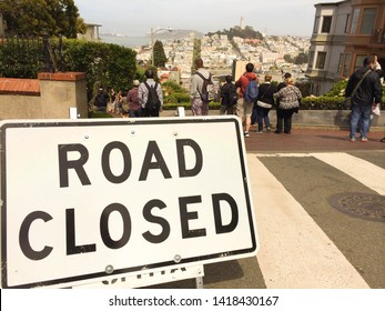 """San Francisco/California/USA - July 4 2014 : Street signs written  """"Road Closed"""" on the Lombard Street in San Franscisco Bay Area rounded by people"""