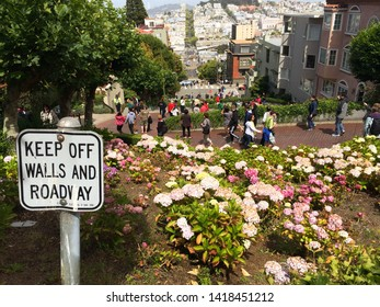 """San Francisco/California/USA - July 4 2014: Street sign written """"keep off wall and roadway"""" on lombard street - San Francisco in the 4th july california summer"""