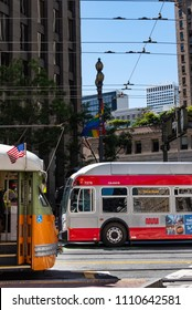 SAN FRANCISCO,CA/U.S.A. - JUNE 2, 2018: A photo of a muni bus and historic streetcar crossing paths nose-to-nose on Market Street.
