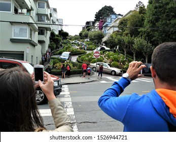 San Francisco,June 20,2018 a couple of curious tourists watch the cars descend from the Lombard street