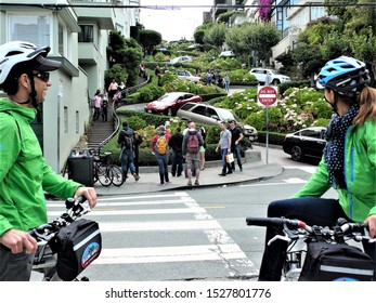 San Francisco,June 20,2018 two cyclists look intrigued by the machines running on the Lombard street