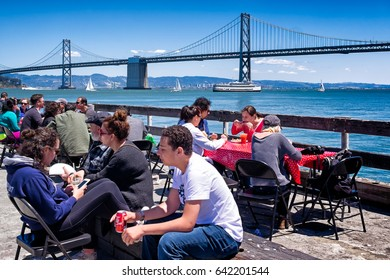 SAN FRANCISCO-May 13, 2017: People eating at tables on the Ferry Building pier during the popular Saturday farmers market, a foodie destination. Bay Bridge, sailboats and a tour boat in the background
