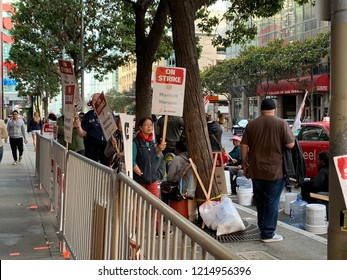 "SAN FRANISCO, CA - October 27, 2018. ""One Job Should Be Enough"" picketing signs held by Marriott hotel employees in downtown SF, demanding higher wages and increased benefits from their employer."