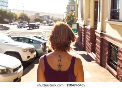 San Fransisco, California / USA - 09.22.2019: A caucasian woman with a tattooed neck walks down a street in harsh sunlight.
