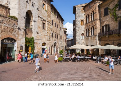 SAN GIMIGNANO, ITALY - 27th of August 2014: Tourists walk in San Gimignano, Italy. The Historic Centre of San Gimignano is a UNESCO World Heritage Site on 27th of August 2014 in SAN GIMIGNANO, ITALY