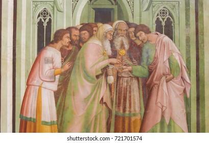 SAN GIMIGNANO, ITALY - JULY 11, 2017: Judas receives thirty pieces of silver to betray Jesus. Fresco in the Collegiata of San Gimignano, Italy.