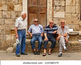 San Gimignano, Italy - July 29. 2018: Group of Italian men sitting in the main square and discussing important issues.