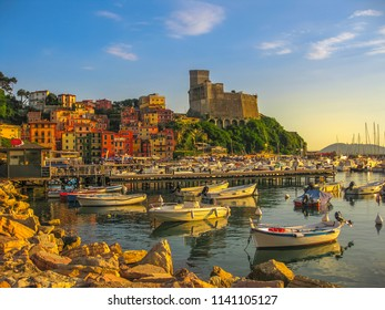 San Giorgio castle of Lerici town from the of Gulf of Poets with sailing boats and motor boats at sunset. La Spezia province, Ligurian Coast of Italy. Scenic Lerici Port with pedestrian jetty.